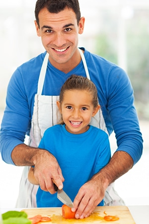 happy father daughter cooking together