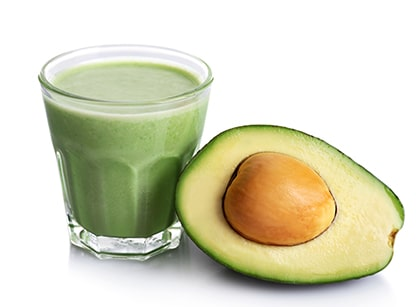 Glass of fresh avocado smoothie and avocado fruit isolated on wh